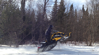 Snowmobile with skis in the air